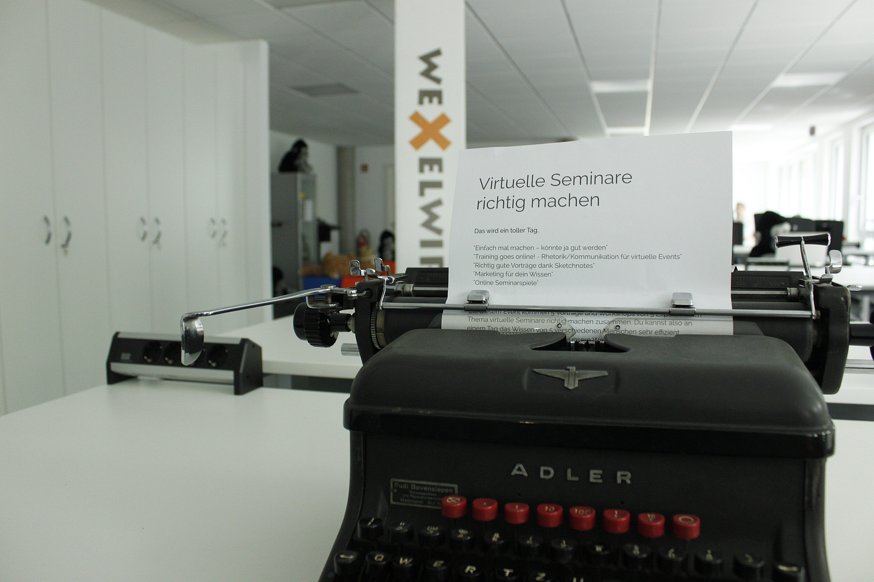 Schreibmaschine mit einem Blatt auf dem der Titel der Veranstaltung steht